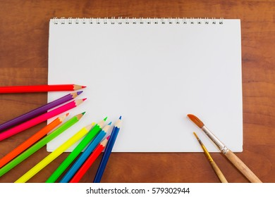 Album for drawing, a white paper on the table, on the wooden background. Pencils