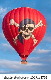 Albuquerque, New Mexico - October 5, 2016: Albuquerque, New Mexico - October 5, 2016: Colorful red hot air balloon with pirate skull and cross bones face floating in the morning sky.