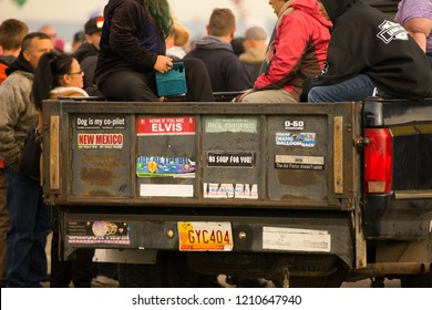 Albuquerque, New Mexico / USA - October 13, 2018: Bumper stickers on a truck tailgate with truck bed filled with people and others walking about at the Albuquerque Balloon Fiesta