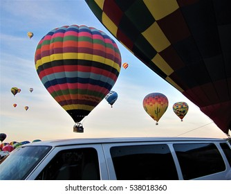 Albuquerque, NM, USA - October 2, 2011: Hot air balloons lifting off from ground above van during Balloon Fiesta 2011.