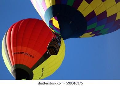 Albuquerque, NM, USA - October 7, 2016: Two hot air balloon sail past at dramatic angle during Balloon Fiesta 2016.