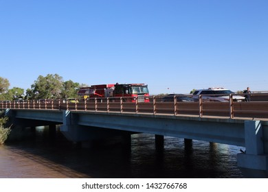 Albuquerque, NM/USA - June 23, 2019:  Firefighters and emergency rescue waiting on the old Alameda bridge over the Rio Grande responding to call regarding individuals on floatation tubes in distress.