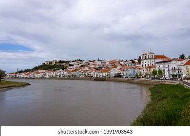 Alcacer do Sal/Portugal - April 13 2019: The river Sado running past the white houses and castle of the Alentejo market town of Alcacer do Sal.