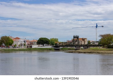 Alcacer do Sal/Portugal - April 13 2019: Alcacer do Sal bridge  across the Sado river in Alentejo, Portugal. In the foreground is the river Sado and on the left some