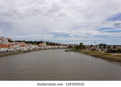 Alcacer do Sal/Portugal - April 13 2019: The river Sado running past the white houses and castle of the Alentejo market town of Alcacer do Sal. There are boats on the river.