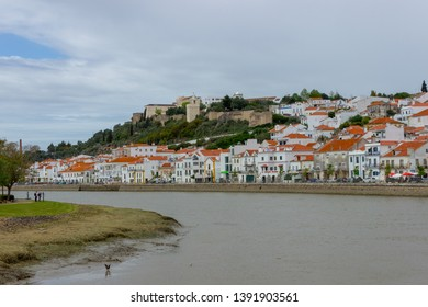 Alcacer do Sal/Portugal - April 13 2019: The river Sado running past the white houses and castle of the Alentejo market town of Alcacer do Sal. Viewing north from the south bank of the river.