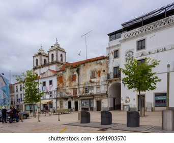 Alcacer do Sal/Portugal - April 13 2019: The twin towers of the Igreja de Santiago seen over the rooftops of waterfront houses in Alcacer do Sal, Portugal.