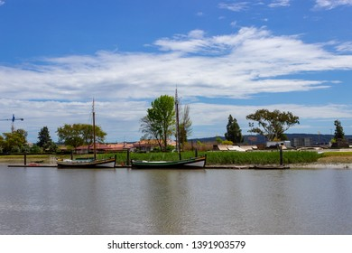 Alcacer do Sal/Portugal - April 13 2019: Two traditional river Sado sailboats docked on the south bank of the river Sado opposite Alcacer do Sal, Alentejo, Portugal.