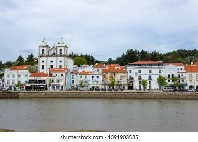 Alcacer do Sal/Portugal - April 13 2019: The twin towers of the Church of St James (igreja de Santiago) seen over the rooftops of waterfront houses in Alcacer do Sal, Portugal.