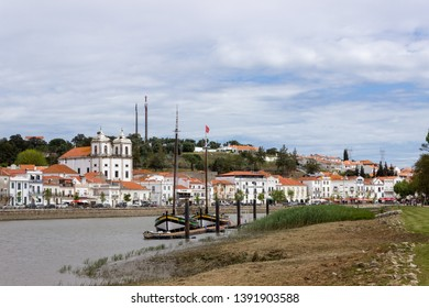 Alcacer do Sal/Portugal - April 13 2019: Two colorful wooden sailing boats docked on the river Sado flowing through the picturesque town of Alcacer do Sal