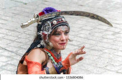 ALCALA DE HENARES, SPAIN - OCTOBER 12th 2019: Sacred dances. Neftis. Beautiful woman dancing with a saber over her head, in San Diego square, during the week of cervantino medieval street market.