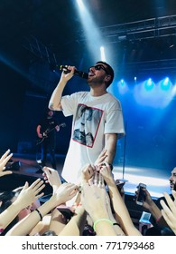 Alcatraz dance club, MI, Italy - Dic 2, 2017: the popular singer Coez during his sold out at the Alcatraz in Milan, Italy. In the foreground outstretched arms of the audience.