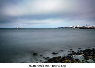Alcatraz Island in San Francisco with smooth water effect on cloudy day. view direction prison and city below golden gate bridge with calm water at shore