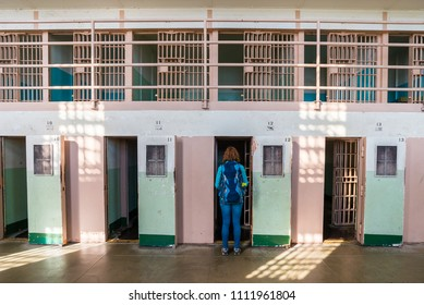 Alcatraz island / United States of America - May 11 2018:  Young woman is observing prison cells in Alcatraz prison in San Francisco, United States of America