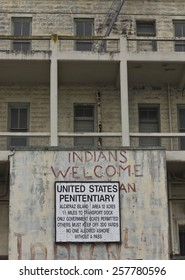 ALCATRAZ, USA - AUGUST 12 2013: Arriving in Alcatraz Penitentiary. External view of the building in a dull day in the summer season. Entrance sign detail with an old graffiti