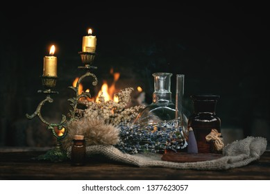 Alchemist table. Magic potion bottles and dried herbs on a table on a burning fire background. Witchcraft, witch doctor concept.