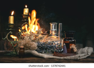 Alchemist or witch doctor table. Magic potion bottles and dried herbs on a table on a burning fire background. Witchcraft concept.