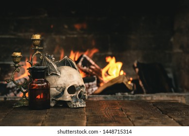 Alchemist or wizard or witch doctor table with magic accessories above on a burning fire background.