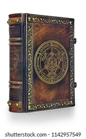 Alchemy leather book with gilded transmutation circle attributed to a German alchemist from the 17th century. The book is captured little from the left side, isolated while stand up on the table.