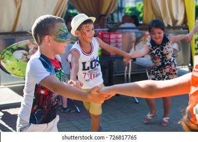 Alchevsk, Ukraine - July 27, 2017: Happy children play with animators in summer -