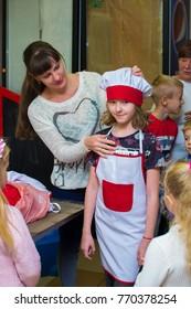 Alchevsk, Ukraine - September 24, 2017: School cook for children. Preparing pizza