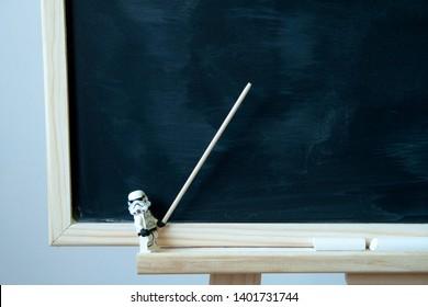 Alcobendas, Spain - April 12, 2017:  lego minifigure of a starwars stormtrooper showing something on blackboard, appointing gesture.