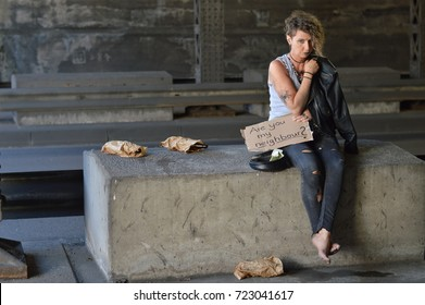 alcohol addicted, homeless and unemployed woman begging for money holding a sign - are you my neighbor?
