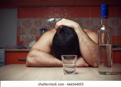 Alcohol addicted man sleeping at the table. Sad depressed male adult having troubles with alcohol.