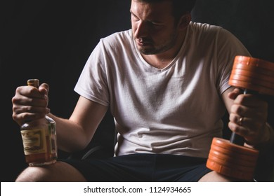 Alcohol addiction interferes with sports, breaks down life. portrait of a young sad man who is holding a bottle and alcohol and a dumbbell