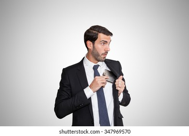 Alcohol addiction possesses this young business man hiding his alcohol flask in his jacket.