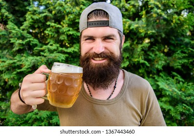 Alcohol and bar concept. Creative young brewer. Craft beer is young, urban and fashionable. Distinct beer culture. Hipster brutal bearded man hold mug cold fresh beer. Man enjoying beer in summer.