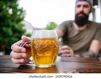 Alcohol and bar concept. Creative young brewer. Craft beer is young, urban and fashionable. Distinct beer culture. Mug cold fresh beer on table close up. Man sit cafe terrace enjoying beer defocused.