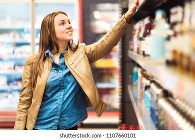 Alcohol or beverage shelf in supermarket or liquor store. Woman looking at alcoholic drinks or sodas in shop. Happy female customer buying groceries.