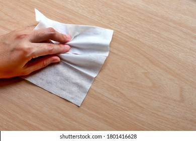Alcohol clean pad wiping and cleaning wooden table for disinfect virus bacteria, prevent from epidemic of disease during the corona virus outbreak. - Shutterstock ID 1801416628