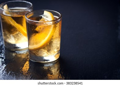 Alcohol cocktail with brandy, whiskey, lemon and ice in small glasses, selective focus