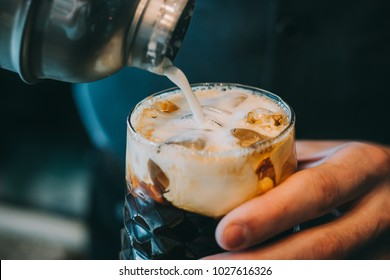 Alcohol cocktail on the bar. Bartender making an alcoholic cocktail. Irish cofee