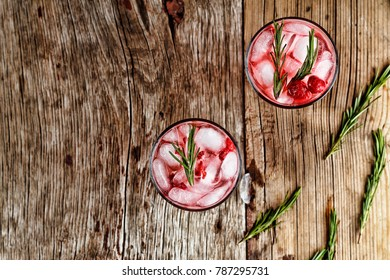 Alcohol cocktail with rosemary on a wooden table, top view
