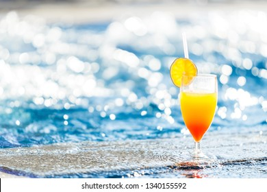 alcohol cocktail with a slice of an orange on the glass standing at the edge of a resort pool. Concept of luxury vacation. free space for advertising text