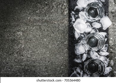 Alcohol and cocktails. Three glasses of vodka on a slate tray, with ice. On a black stone table, Copy space top view