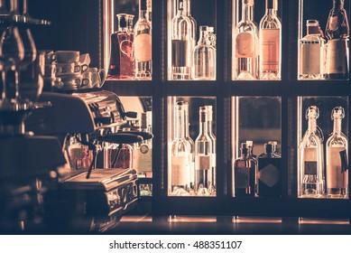 Alcohol and Coffee Bar Closeup. Bar Shelf Full of Alcohol Bottles and Professional Espresso Coffee Maker