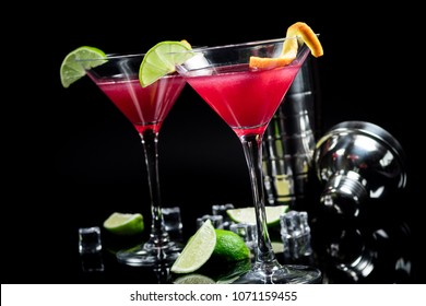 Alcohol drink cocktail Cosmopolitan with lime on black background