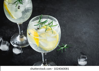 Alcohol drink (gin tonic cocktail) with lemon, rosemary and ice on rustic black stone table, copy space, top view. Iced drink with lemon.