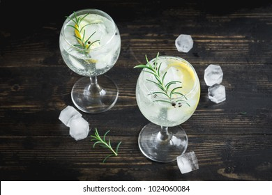 Alcohol drink (gin tonic cocktail) with lemon, rosemary and ice on rustic black wooden table, copy space, top view. Iced drink with lemon.