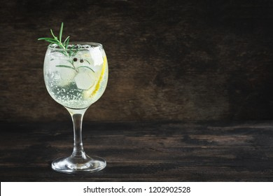 Alcohol drink (gin tonic cocktail) with lemon, rosemary and ice on rustic black wooden table, copy space. Iced cocktail drink with lemon and herbs.