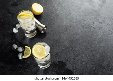 Alcohol drink (gin tonic cocktail, vodka cocktail, tom collins cocktail) with lemon and ice on rustic black stone table, copy space, top view. Iced soda drink with lemon.