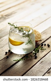 Alcohol drink (gin tonic cocktail) with lemon, juniper branch,  and ice on rustic wooden table, copy space. Iced cocktail drink with lemon and juniper berries.