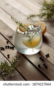 Alcohol drink (gin tonic cocktail) with lemon, juniper branch, and ice on rustic wooden table, copy space. Iced cocktail drink with lemon.