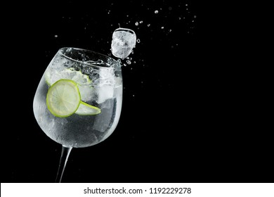 Alcohol drink margarita splash with lime and ice cube on a black background