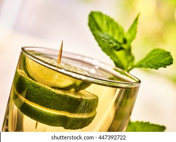 Alcohol drink. On wooden boards is glass with alcohol green transparent drink. A drink number eleven cocktail mohito with slice lime and mint leaf. Country life. Light background. Slanted angle.
