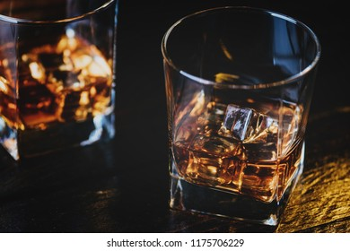 Alcohol drink whisky, whiskey or bourbon with ice cubes on dark wood table
